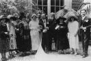 Sposi e parenti posano per una fotografia ricordo in esterno, inizi Novecento